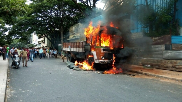 Vehicles with Tamil Nadu numbers were torched and burned by protesters in Bengaluru. (Photo: IANS)