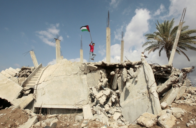 A man upholds the Palestinian flag among destruction in the Gaza strip. (Photo: Reuters)