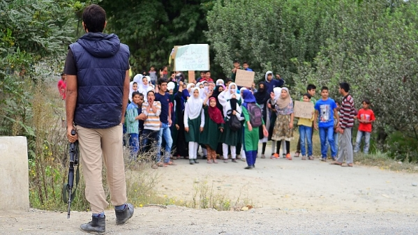 Children protesting against the government on the outskirts of Srinagar as a Jammu and Kashmir Police official looks on. Most schools and colleges have been shut in the Valley since the agitation began in July. (Photo: Jaskirat Singh Bawa)