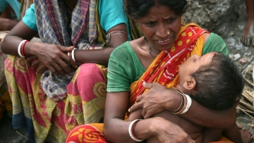 A woman grasps her child in the wake of Cyclone Aila in West Bengal in 2009. (Photo: Reuters)