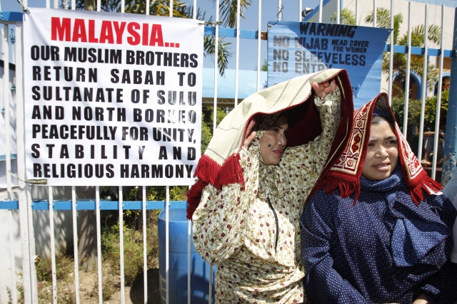 Followers of the Sultan of Sulu stand in front of a banner for liberation of Sabah. (Photo: Reuters)
