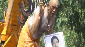 A man is seen hanging from hooks holding Amma's  photograph as prayer for her health. (Photo courtesy: <i>The News Minute</i>)