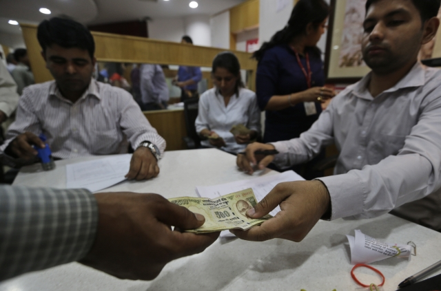 A man gives discontinued currency notes to exchange them with newly introduced currency notes in a bank in New Delhi. (Photo: AP)