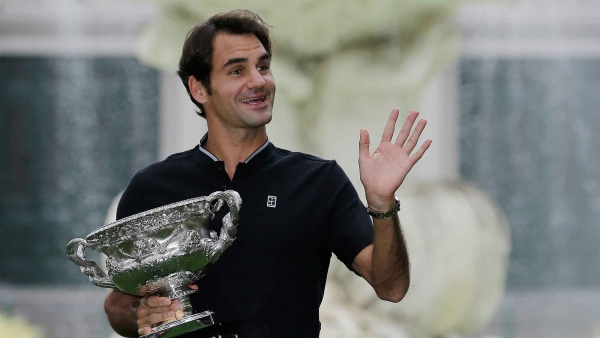 Switzerland's Roger Federer waves to fans as he holds his Australian Open trophy at Carlton Gardens in Melbourne, Australia. (Photo: AP)