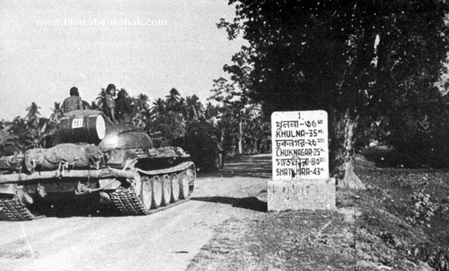 An Indian T-55 tank of 'B' Squadron, 63 Cavalry, leading the road to Khulna from Jessore - 35 miles away, says the stone post at left. It was not a cake walk, as the Pakistan Army put up a stiff and determined opposition at Khulna.