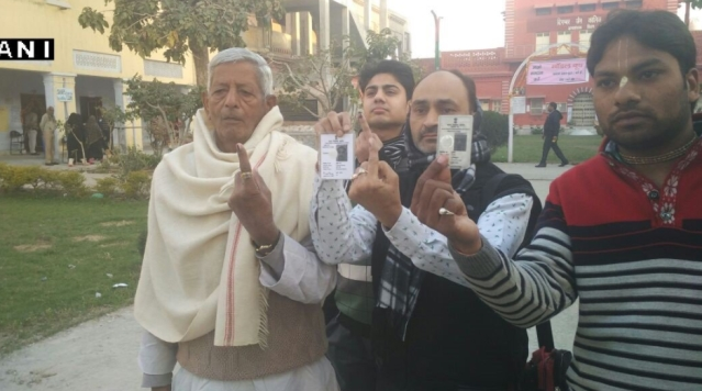 People show their inked fingers and voter IDs after casting their votes in Baghpat. (Photo: ANI)