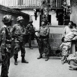 Indian forces during a house search in Srinagar, 1993. (Photo Courtesy: <i>Witness: Kashmir 1986-2016</i>/Meraj Ud Din)