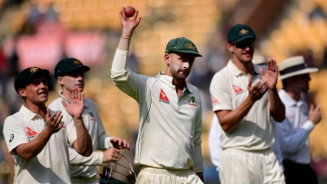 Australia's Nathan Lyon celebrates with teammates after taking eight wickets during the first day of the second test match against India at Chinnaswamy Stadium. (Photo: PTI)
