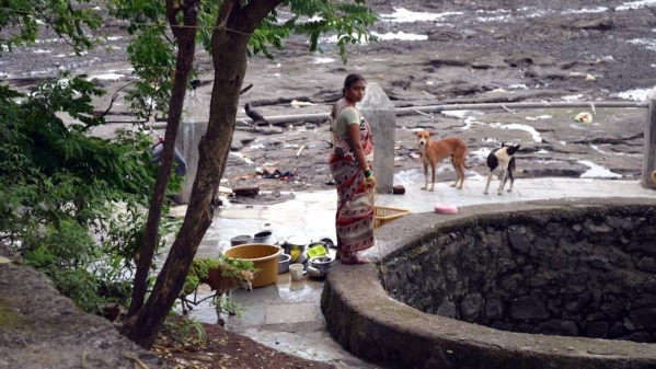 "A village woman in Elephanta cleans household utensils at a well that barely contains any water. (Photo Courtesy: Gajanan Khergamker/<a href=""http://www.villagesquare.in/2017/03/31/development-distant-dream-elephanta-island/"">Village Square</a>)"