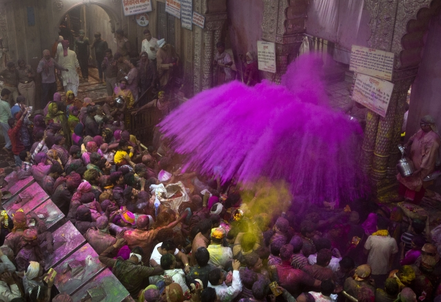Hindu priests throw color powders at the devotees inside Banke Bihari temple. (Photo: AP)