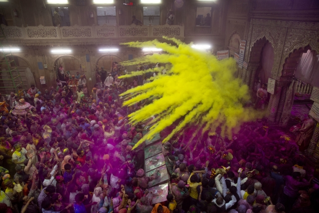 Hindu devotees throw colored powder on each other inside Banke Bihari temple. (Photo: AP)