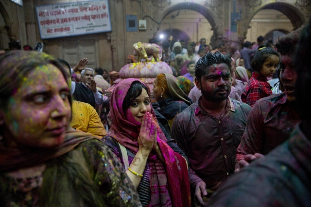 Hindu devotees smeared with colours pray inside Banke Bihari temple. (Photo: Ap)