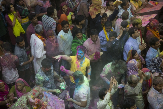 Hindu devotees throw colored powders on each other inside Banke Bihari temple during Holi festival celebrations in Vrindavanon March 8, 2017. (Photo: AP)