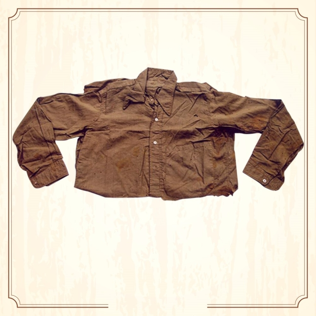 "<a href=""http://www.supremecourtofindia.nic.in/sciphoto/photo_m1.html#""></a> Shirt of Bhagat Singh. A full sleeves khaki shirt with Italian collar, marked Bhagat Singh on the collar. (Image Altered by The Quint/Original Photo Courtesy: <a href=""http://www.supremecourtofindia.nic.in/sciphoto/photo_m1.html"">Supreme Court of India)</a>"