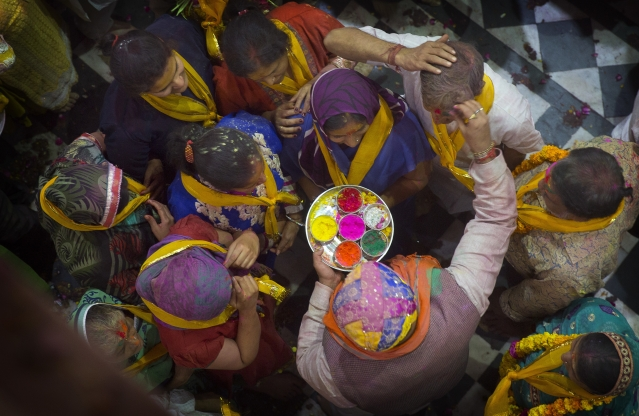 A Hindu priest applies colors to a devotee as others wait inside Banke Bihari temple. (Photo: AP)