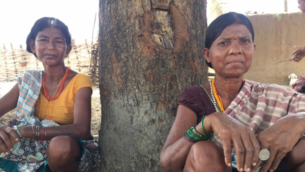 Markam Budri (right) and another tribal woman sit on their haunches under the shade of a towering Mahua tree. Image used for representation only.