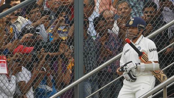 India's Sachin Tendulkar arrives to bat as fans try to take pictures during the third day of their third test cricket match against West Indies in Mumbai November 24, 2011.