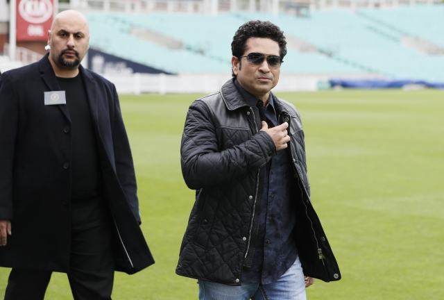Sachin Tendulkar is escorted by a security officer as he arrives at the Oval cricket ground. (Photo: AP)