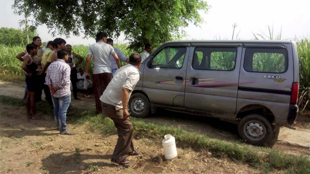 Villagers look on as police investigate near the vehicle, Maruti Suzuki Eeco, in which seven members of family along with a driver were travelling while being attacked. (Photo: PTI)