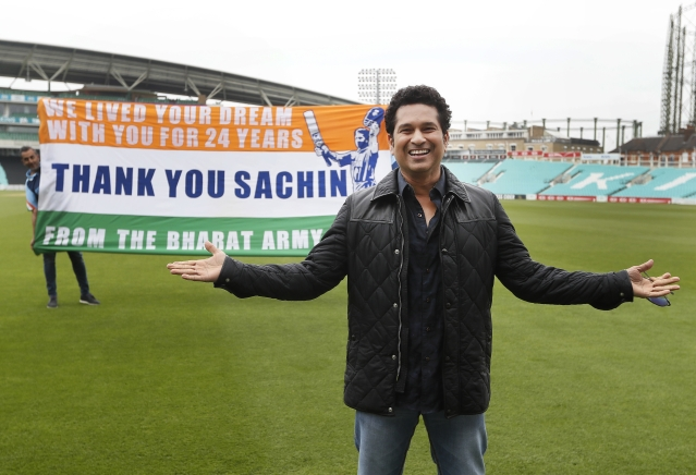 Sachin Tendulkar smiles in front of a flag held up by fans, on the pitch at the Oval cricket ground. (Photo: AP)