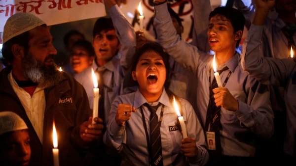 Schoolchildren shout slogans as they hold candles during a candle light vigil to mark the first anniversary of the Delhi gangrape. (Photo: Reuters)