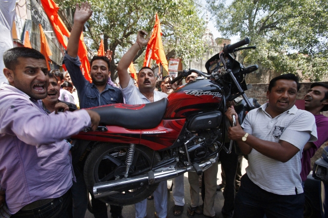 Activists from Shiv Sena, a Hindu hardline group, carry a motorcycle as they shout slogans during a protest against the price hike in petrol, in Jammu May 24, 2012. (Photo: Reuters)