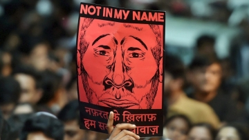"A protester holds up a ""Not in My Name"" placard at Jantar Mantar in New Delhi."