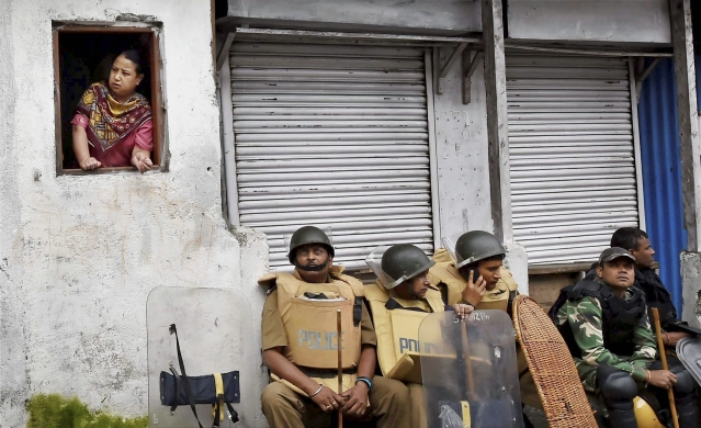 Security personnel sit as a woman looks out of a window in Darjeeling on Sunday. (Photo: PTI)