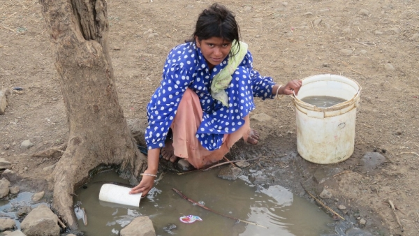 A young woman fills her bucket with dirty water fearing that the handpump might give out anytime.