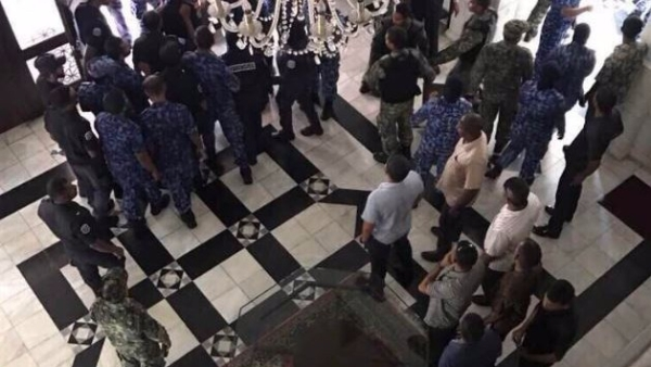 MPs being forcefully removed from the Maldives Parliament.