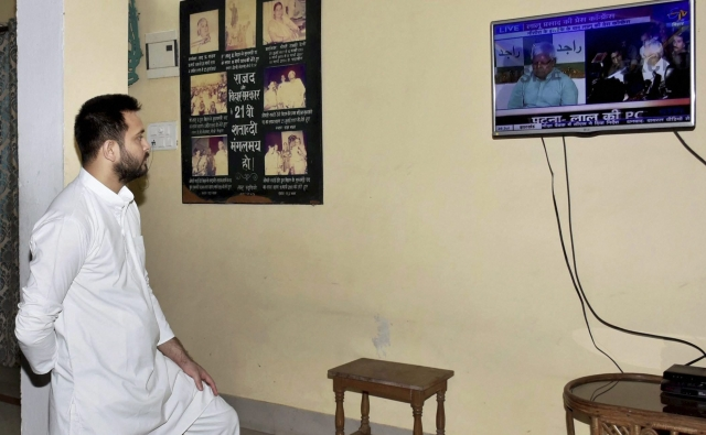 Bihar Deputy Chief Minister Tejashwi Yadav watching TV after Nitish Kumar resigned as Chief Minister in Patna on Wednesday.