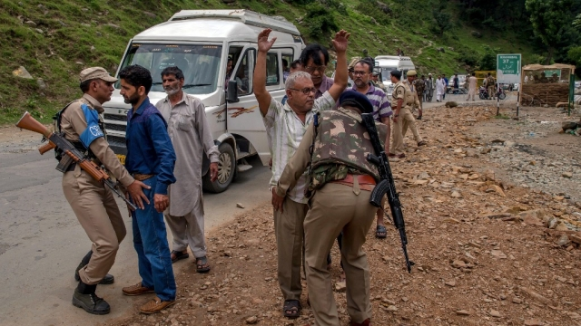 CRPF personnel frisk a Kashmiri civilian (left) and an Indian pilgrim (right) at a temporary checkpoint near the base camp in Pahalgam,   Kashmir, 11 July 2017.