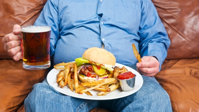 Put that fry down! Binge-eating junk and being a couch potato will do no good to your skin.