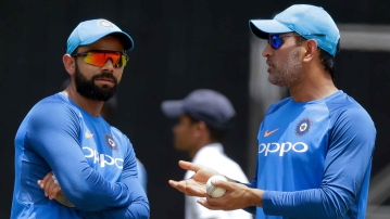 Virat Kohli and MS Dhoni have a chat during a training session.
