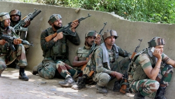Army soldiers take positions outside a house where militants were hiding during an encounter in which top three Hizbul Mujahideen Commanders and two Army soldiers were killed, at Awneera in Shopian district of south Kashmir on Sunday.