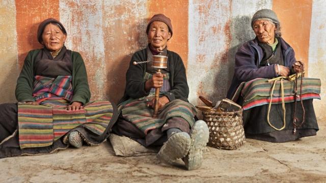 Three Tibetan women praying in Lo Manthang, Nepal.
