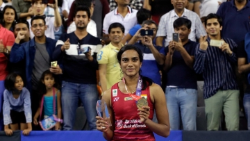 India's Pusarla V. Sindhu poses with a gold and trophy during the awards ceremony after winning against Japan's Nozomi Okuhara during women's single final match at the Korea Open Badminton in Seoul