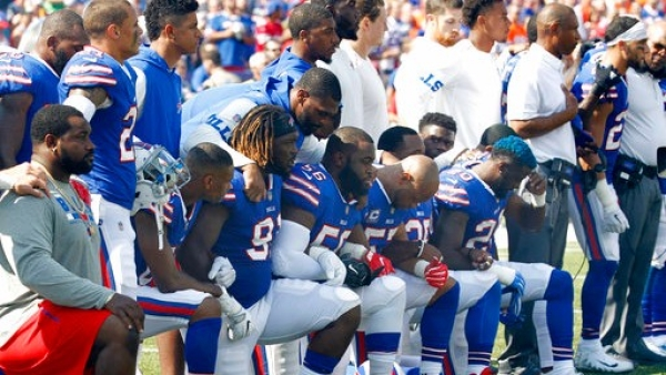 Buffalo Bills players take a knee during the playing of the national anthem prior to an NFL football game against the Denver Broncos on Sunday 24 September 2017, in Orchard Park, New York.