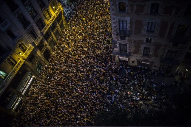 Demonstrators gather next to the city's major Spanish police station in downtown Barcelona, Spain, Tuesday Oct. 3, 2017. Thousands of people demonstrated against the confiscation of ballot boxes and charges on unarmed civilians during Sunday's referendum, declared illegal by Spain's Constitutional Court, on Catalonia's secession from Spain.