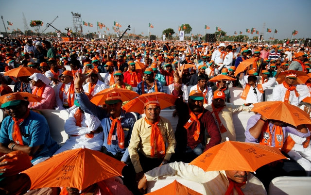 Supporters of India's ruling Bhartiya Janta Party (BJP) wait for Prime Minister Narendra Modi to address a public rally at Bhaat village on the outskirts of Ahmedabad, India October 16, 2017.