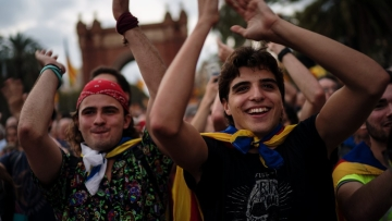 Pro-independence supporters club hands as they take part in a rally in Barcelona, Spain, on Tuesday, 10 October.