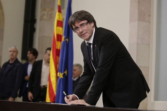 Catalan regional President Carles Puigdemont signs an independence declaration document after a Parliamentary session in Barcelona, Spain on Tuesday, 10 October.