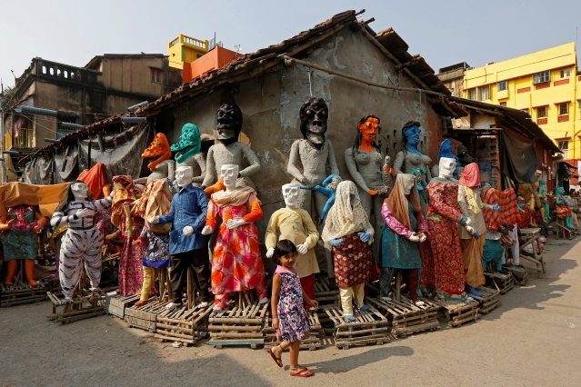 A girl walks past clay idols of the Hindu mythological characters 'Dakinis' and 'Yoginis', who will be worshipped along with the Hindu goddess Kali during the Kali Puja festival, at a roadside workshop in Kolkata, India October 17, 2017.