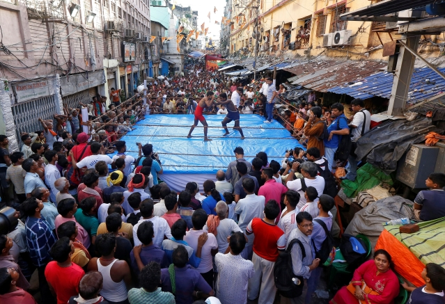 Wrestlers fight during an amateur wrestling match inside a makeshift ring installed on a road organised by local residents as part of Diwali, the festival of lights, celebrations in Kolkata, India, October 18, 2017.