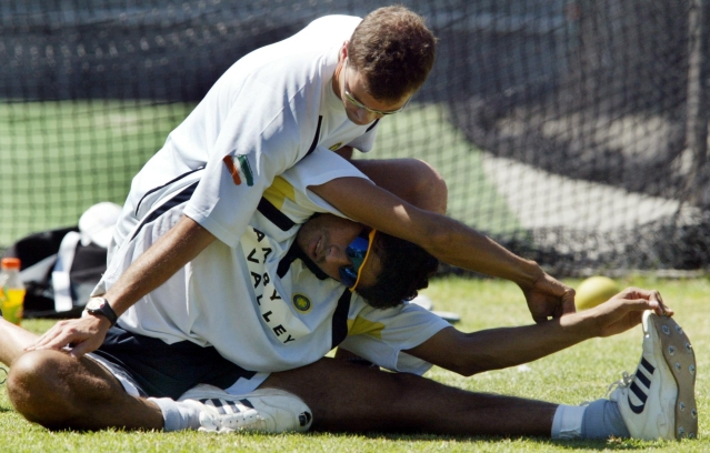 India's physiotherapist Andrew Leipus helps Ashish Nehra to work out during a practice session in Cape Town, March 6, 2003.