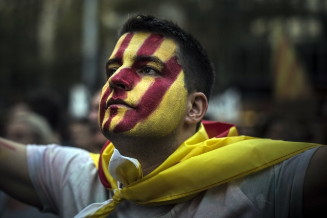 A man with the Catalan flag painted on his face attends a demonstration downtown Barcelona, Spain on Tuesday, 3 October 2017.