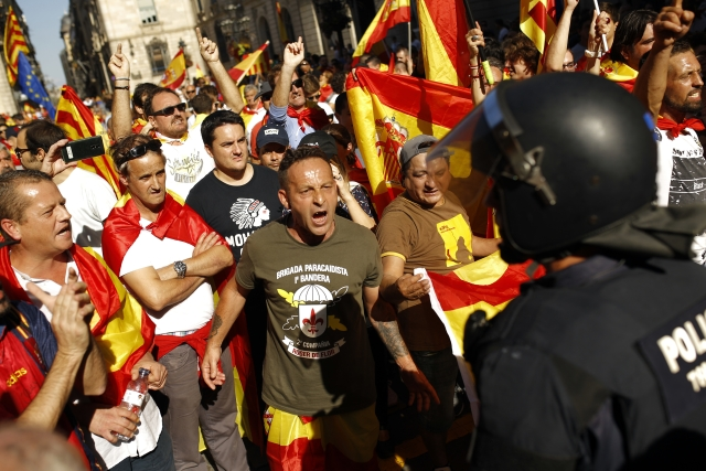 Demonstrators challenge Catalan Mossos d'Esquadra regional police officers at the end of a march in downtown Barcelona, Spain, to protest the Catalan government's push for secession from the rest of Spain, Sunday, 8 October 2017.