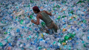 A worker  moves through a pile of empty plastic bottles at a recycling workshop.