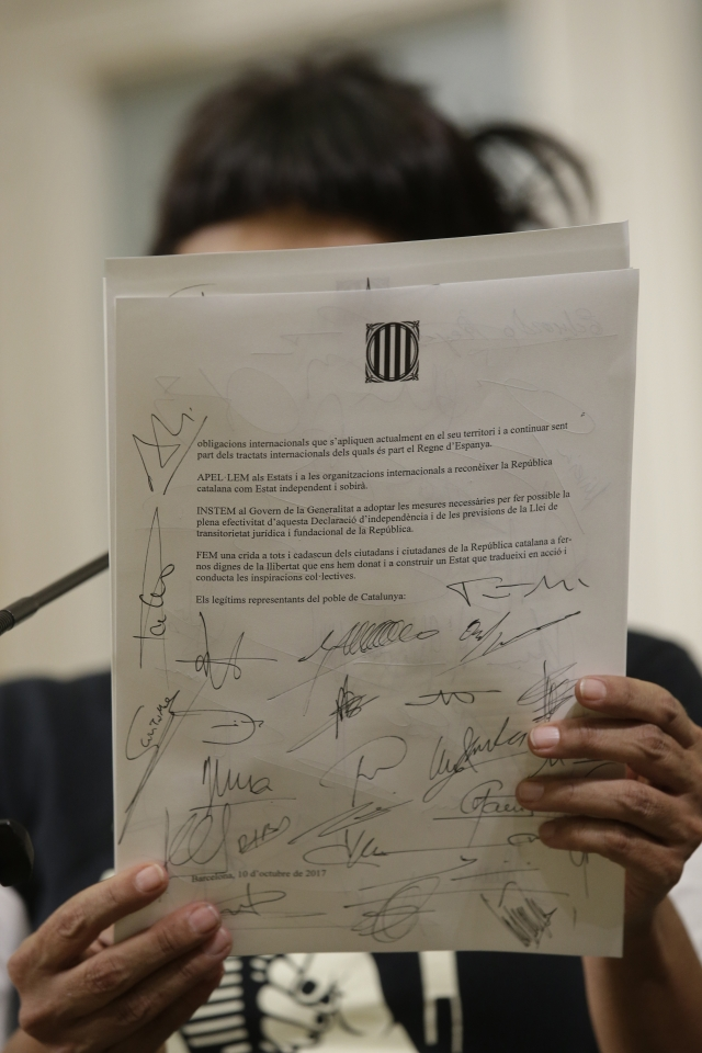 Leader of the collation CUP party, Anna Gabriel holds up an independence declaration document after a Parliamentary session in Barcelona, Spain, on Tuesday, 10 October, 2017.