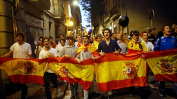 Anti-Catalan independence demonstrators carry a Spanish flag as they march in Barcelona, Spain on Tuesday 3 October 2017.